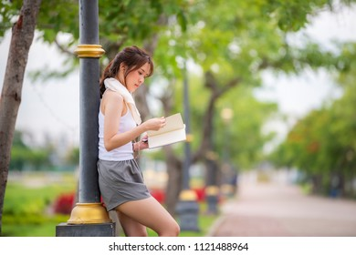 Side view of Beautiful young asian woman holding an open book, reading book in park and leave space for adding your content. Select focus