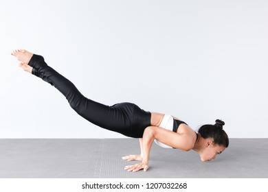 Side view of beautiful young asian woman wearing sportswear practicing yoga in studio,natural light.Concept : Variation yoga poses.Copy space for text.