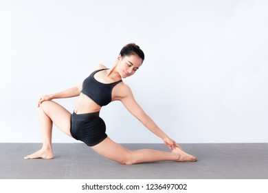 Side view of beautiful young asian woman wearing sportswear practicing yoga in studio,natural light.Concept : Variation yoga poses.Variation of the Low Lunge -Twist Pose.