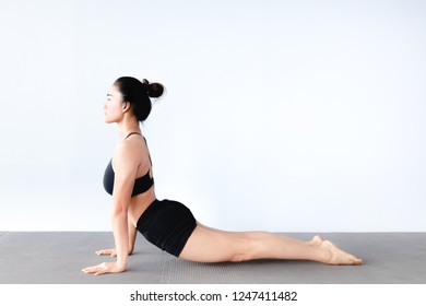 Side view of beautiful young asian woman wearing sportswear practicing yoga in studio,natural light.Concept : Variation yoga poses for beginner.Cobra post (Bhujangasana)Copy space for text.