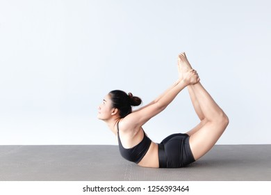 Side view of beautiful young asian woman wearing sportswear practicing yoga in studio,natural light.Concept : Variation yoga poses.Variation of the Bow Pose (Dhanurasana).