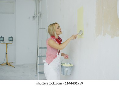 Side view of beautiful young blond woman in white overalls painting plastered wall in pastel yellow color with brush and holding bucket in hand