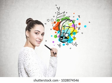 Side view of a beautiful young brunette in a white sweater holding a marker and smiling. A concrete wall background with a colorful lightbulb. An idea concept