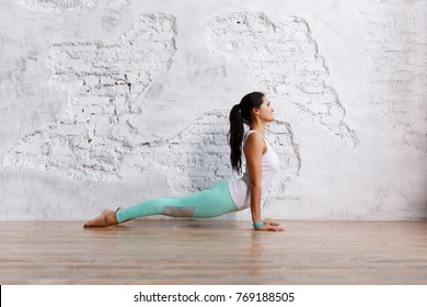 Side view - beautiful young brunette woman in gym clothes makes exercises for stretching  back and legs in an empty gym on white brick wall background. Space for text
