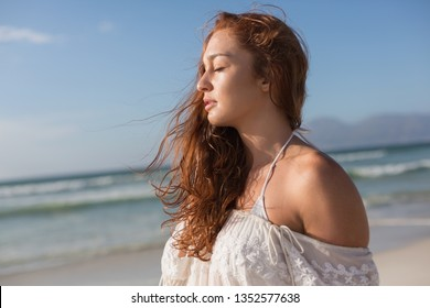 Side view of beautiful young Caucasian woman with eyes closed standing standing on the beach. She seems relaxed