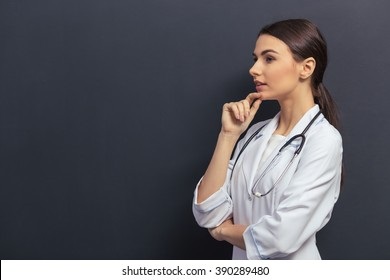 Side view of beautiful young doctor in white medical gown keeping hand on chin and thinking, against blackboard
