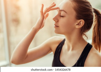 Side view of beautiful young female with closed eyes touching ajna chakra on forehead while doing yoga in gym