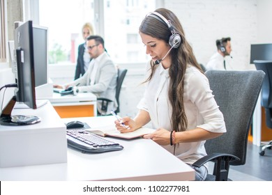 Side view of beautiful young lady working in office. Customer support worker taking notes while talking with client via headset at office desk.