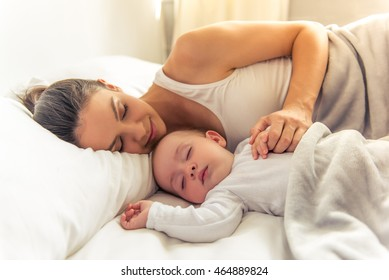 Side view of beautiful young mom and her cute little baby sleeping in bed at home