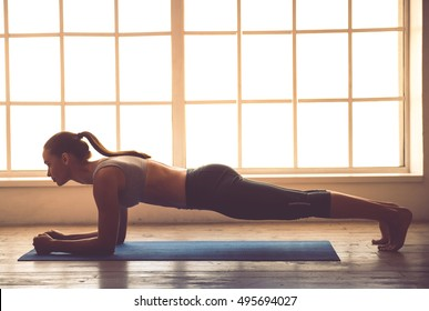 Side view of beautiful young sports lady doing plank in fitness hall