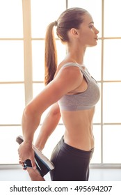 Side view of beautiful young sports lady working out in fitness hall