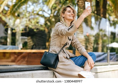 Side view of beautiful young woman smiling while holding smartphone and making self portrait, strolling outdoor in the city street against palms. Happy female taking selfie on mobile phone. Travel