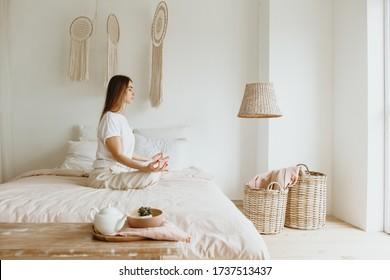 Seitenansicht der schönen jungen Frau, die Meditation auf dem Bett zu Hause praktiziert.
