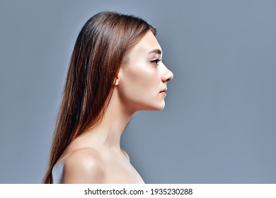 Side view of beautiful young woman with clean perfect skin. Beauty model portrait with natural nude makeup. Spa, skin care and wellness. Close up, gray background, copyspace.