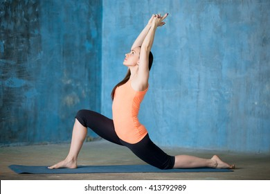 Side view of beautiful young woman dressed in bright sportswear enjoying yoga indoors. Yogi girl working out in grunge interior with blue wall. Doing low lunge exercise, anjaneyasana. Full length