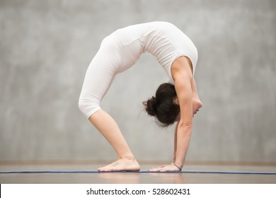 """Side view of beautiful young woman with tattoo on her foot meaning """"Wild kitty"""" working out in fitness club or at home, doing yoga or pilates exercise. Advanced Bridge pose, chakrasana. Full length"""