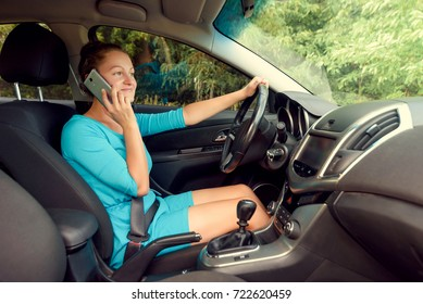 Side view of beautiful young woman driving a car and talking on smart phone, free space. Business woman sitting in car with cell phone,  looking on road