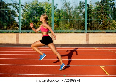 Side view beautiful young woman exercise jogging and running on athletic track on stadium