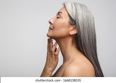 Side view beauty portrait of an attractive sensual mature topless woman with long gray hair standing isolated over gray background, eyes closed
