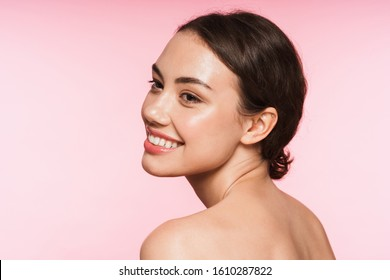 Side view beauty portrait of a beautiful smiling young topless brunette woman standing isolated over pink background