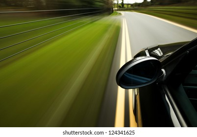 Side view of black car driving in forest road
