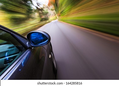 Side view of black car driving fast.