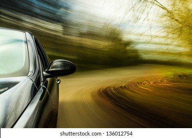 Side view of black car in turn with blurred motion.