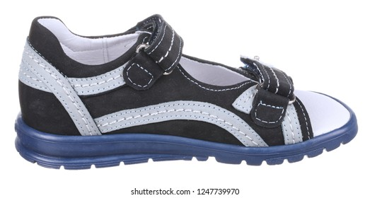 Side view of black, gray, blue and white suede boy sandal with slits and slots, perforated insole and two velcros, isolated on white
