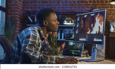 Side view of black man working on computer and editing video with color correction
