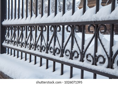 Side view of black metal forged fence covered by snow
