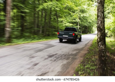 Side view of a black pickup truck in the woods
