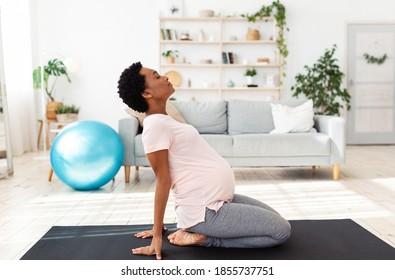 Side view of black pregnant woman doing backbend during meditation or yoga at home. Beautiful African American expectant lady stretching at time of her breathing practice indoors