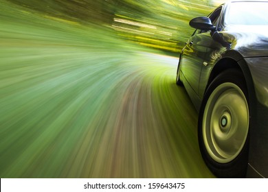 Side view of black sedan driving in forest.