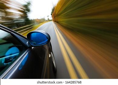 Side view if black sedan driving fast.