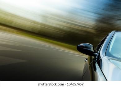 Side view of black sport car in turn.