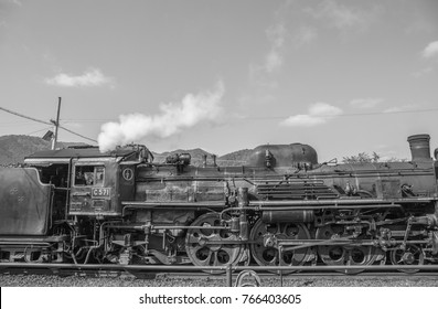 A side view, black and white photo of  a classic steam locomotive emitting white steam like clouds in the sky in the country in Yamaguchi, Japan.