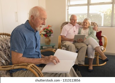 Side view of blind senior man reading a braille book while senior couple using digital tablet at nursing home