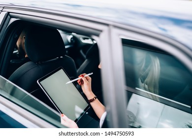 Side view of blond faceless female through open car window sitting with tablet and pen in back seat behind unrecognizable driver