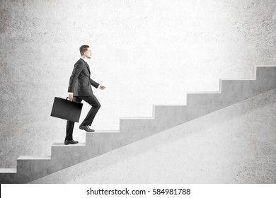 Side view of a blond man in a suit climbing stairs against a concrete wall. Concept of a road to success in business. Mock up
