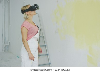 Side view of blond woman in white overalls and pink shirt standing at half-painted pastel yellow wall and looking up in virtual reality headset