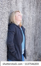 Side view of blonde female leaning against a wall, looking depressed and lonely.