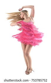 Side view of blonde latino dancer spinning and dancing with flowing hair looking away. Full body length portrait isolated on white background.