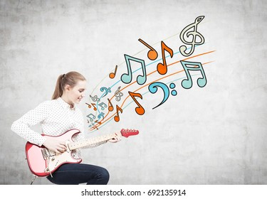 Side view of a blonde woman with a ponytail sitting on a chair and playing an electric guitar. Concrete wall background with colourful music notes on it.