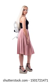 Side view of blonde young stylish fashionable woman with glasses and bag turning and leaving. Full body isolated on white background.