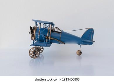 side view of blue metallic biplane retro airplane on white background