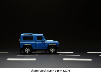 Side view of a Blue Suv which is an old fashioned style on a black background and with road lanes.