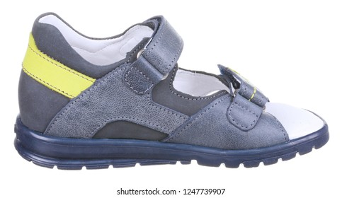Side view of blue and yellow leather and suede boy sandal with slits and slots, perforated insole and two velcros, isolated on white
