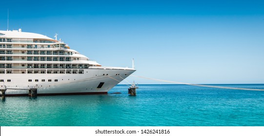Side view and bow of a docked cruise ship on a summer day with clear blue sky.