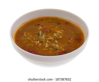 A side view of a bowl of chicken and sausage soup on a white background.
