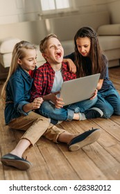 side view of boy and girls using digital laptop at home